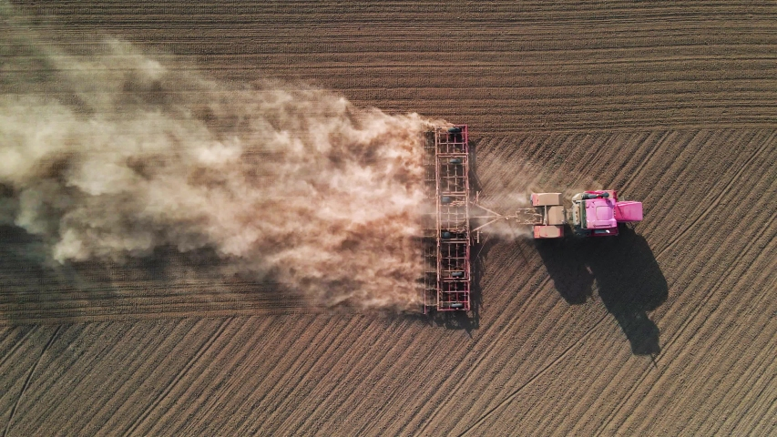Shooting from drone flying high over tractor with harrow system plowing the ground on cultivated farm field, preparing soil for planting new crop next season, agriculture concept, top view | Shutterstock HD Video #1057178497