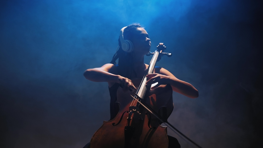 Young beautiful woman playing a melody on cello. Smoky dark studio   Shutterstock HD Video #1057179595