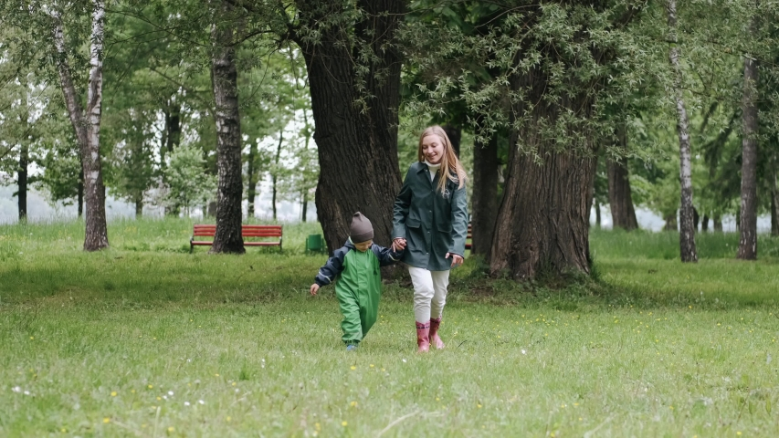 Family in a rainy park. Kids in a puddle. Child having fun outdoors. | Shutterstock HD Video #1057179976