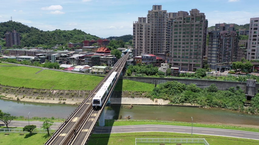 Aerial view of a metro train of Taipei MRT Wenhu Line traveling on a bridge over a riverside park and residential towers standing by the river on a sunny day in Taipei, the capital city of Taiwan Royalty-Free Stock Footage #1057182424