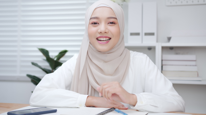 POV of Beautiful Young Asian Muslim Businesswoman leader making a video call remote working online conference with a colleague looking at camera working online. work from home concept. Royalty-Free Stock Footage #1057183189