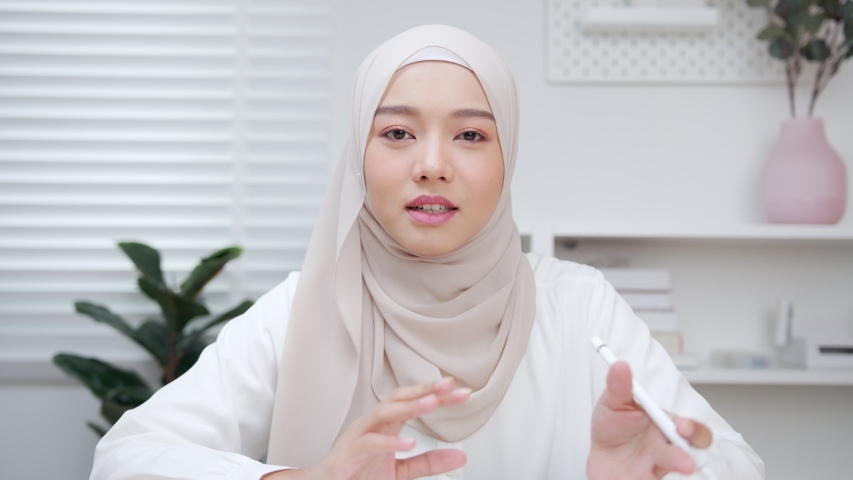 POV of Beautiful Young Asian Muslim Businesswoman leader making a video call remote working online conference with a colleague looking at camera working online. work from home concept. Royalty-Free Stock Footage #1057183201