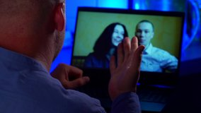 a man communicates via video link with a couple of young people. over-the-shoulder view of the laptop. contour blue light