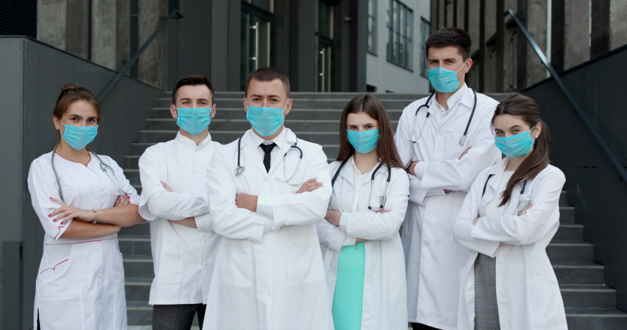 Group of doctors with face masks looking at camera, corona virus concept. Confident team of doctors in face masks standing with their arms folded and looking at camera Royalty-Free Stock Footage #1057186978