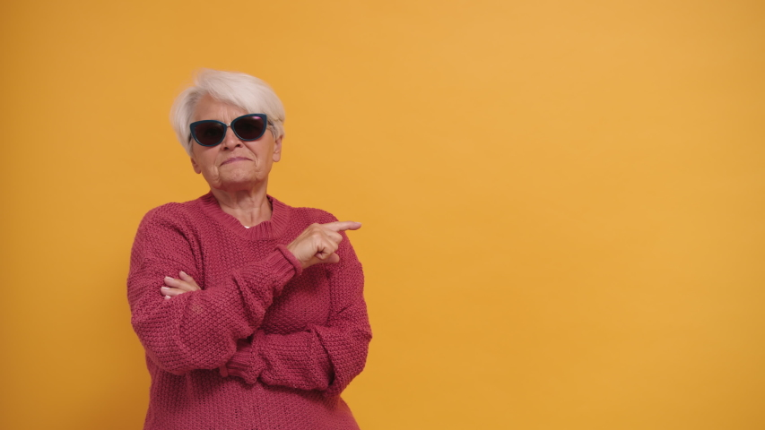 Trendy bossy granny with sunglasses pointing finger on empty space and nodding her head. High quality 4k footage | Shutterstock HD Video #1057188730