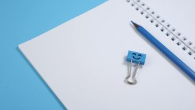 Blank Paper Notepad with Blue Pencils and Smile Binder Clip on Blue Background. Spiral notebook on table. Business, office supplies or education concept