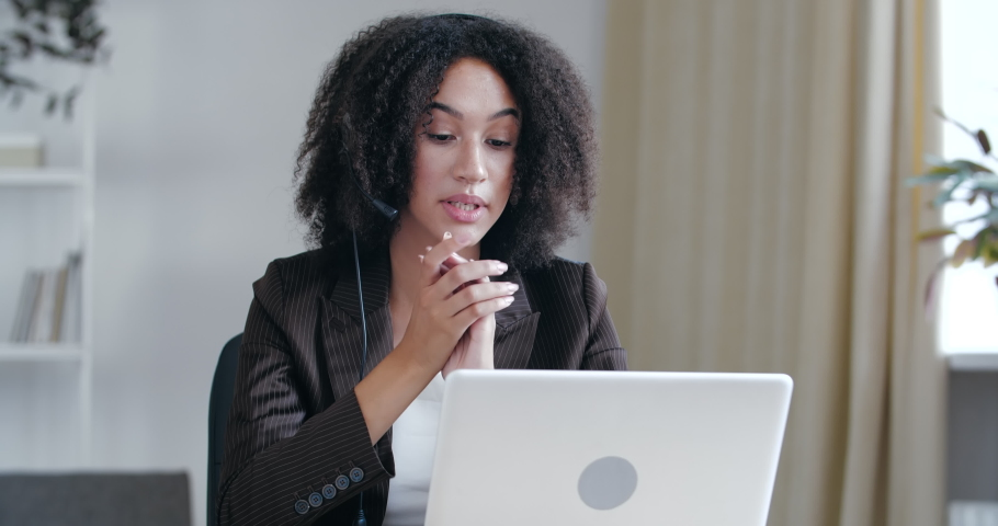 Serious African American woman sitting at desk table uses headphones and webcam laptop computer for communication customer consultation, online sales, video conference support, internet call manager