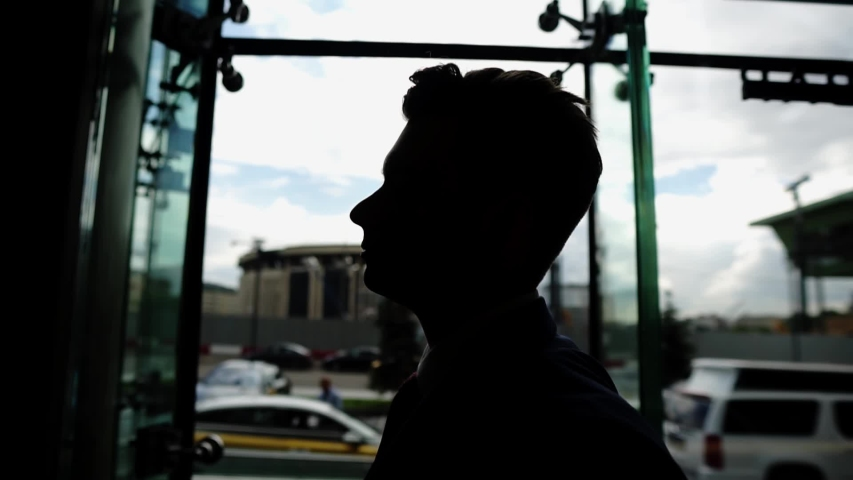 A silhouette of a guy's face in front of a light large window. Outside the window is a big city. | Shutterstock HD Video #1057194859