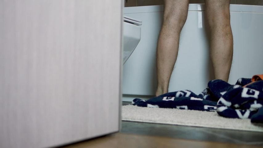 A man takes off his clothes to take a shower,throw things on the bathroom floor,man's legs,close-up. | Shutterstock HD Video #1057197775