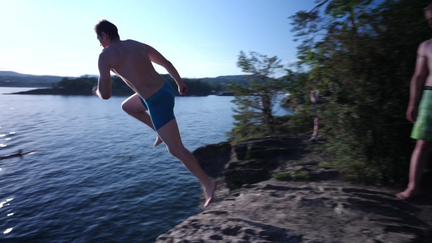 Daring man does a DEATH DIVE into the lake from a cliff   Shutterstock HD Video #1057200757