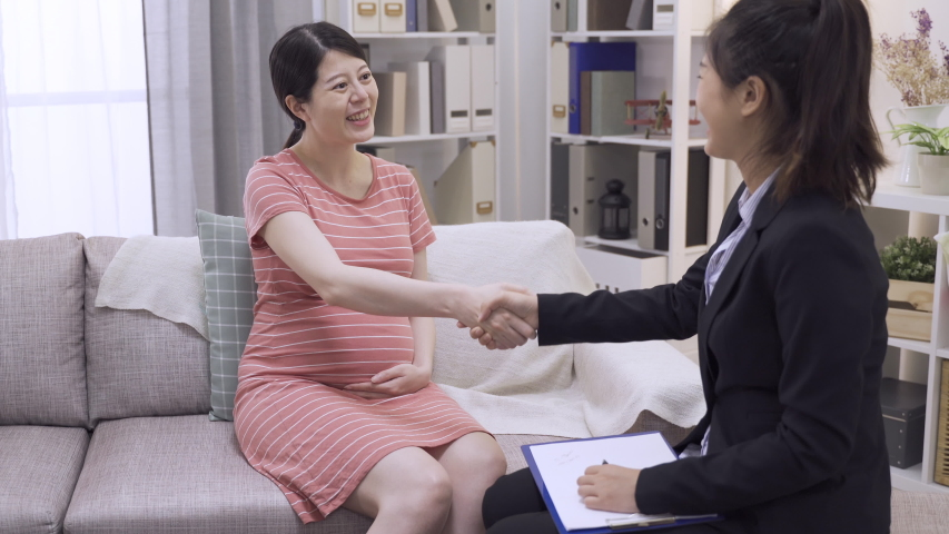 Insurance agent lady worker and pregnant customer shaking hands after signing contract on sofa at home living room. | Shutterstock HD Video #1057203766