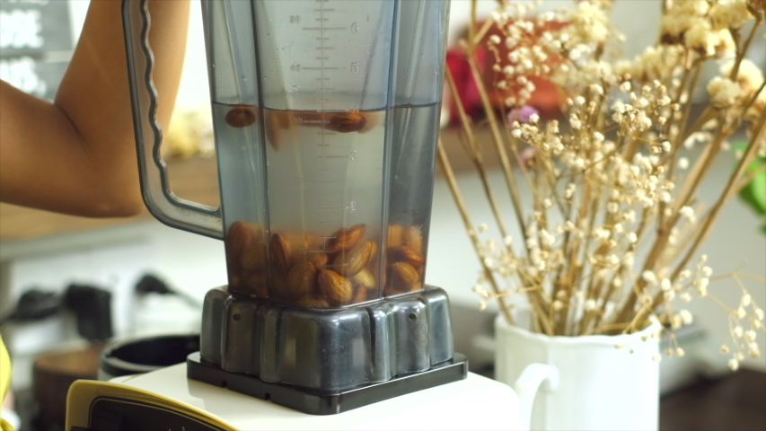 Woman mix grind almonds with water in blender   Royalty-Free Stock Footage #1057205959