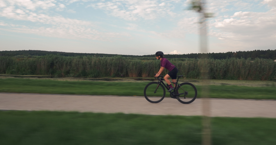 Young woman is cycling fast on bicycle in park. Triathlete rides on bike.