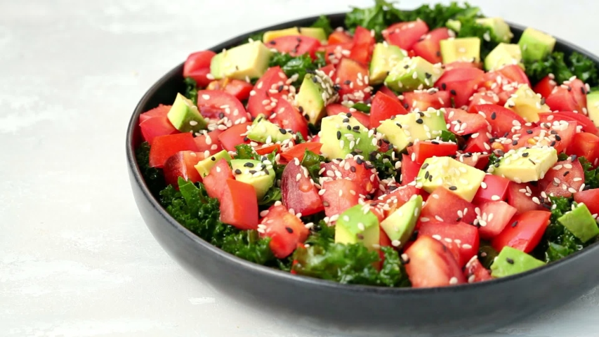 Kale salad with tomatoes and avocado in black plate. Healthy raw vegan lunch concept. | Shutterstock HD Video #1057207765