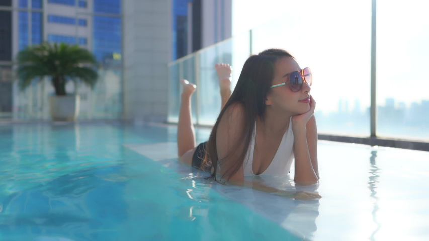 Kickin back in the hotel pool a young attractive woman lies on her stomach and looks out at the city skyline. | Shutterstock HD Video #1057209403