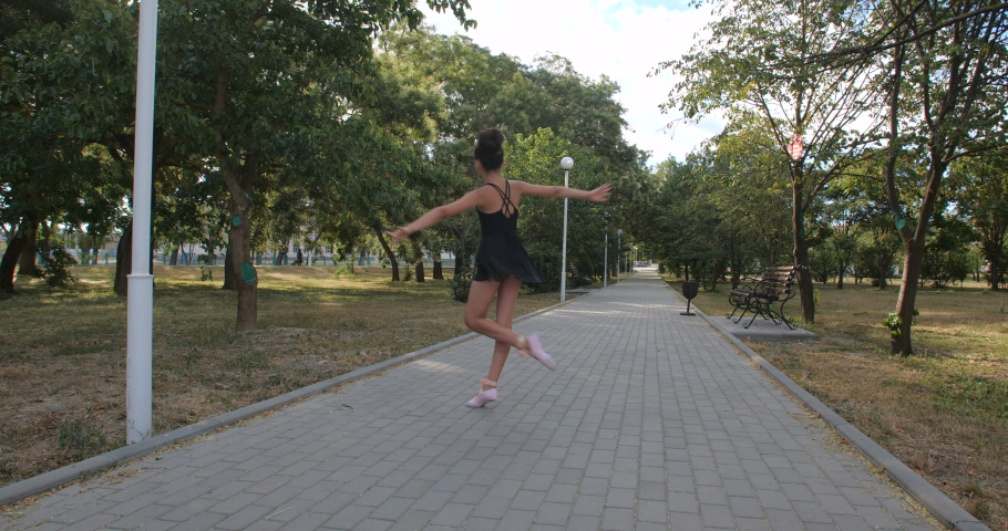 Beautiful Caucasian girl of eight years in black ballet suit dancing ballet. Young ballerina practicing in a city park on a sunny summer day. Slow motion 50 fps 4k | Shutterstock HD Video #1057213420