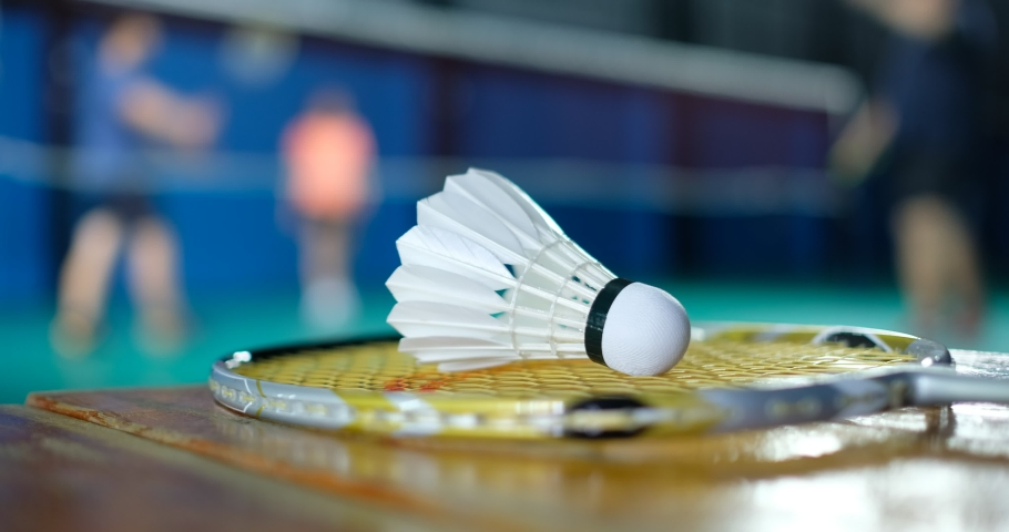 Badminton shuttlecock and racket with blur player background