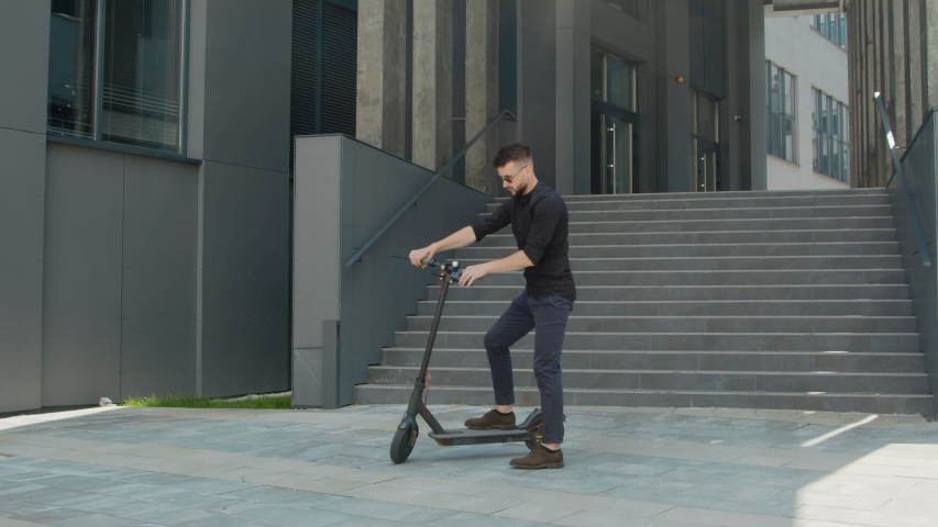 A man who uses an electric scooter for as a vehicle in the city. A man came to a business meeting on an electric scooter. Transport of the future for young people. | Shutterstock HD Video #1057216324