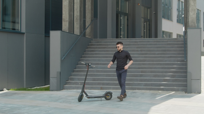 A young man who uses an electric scooter as a modern means of transportation in the city. A male businessman approaches an electric scooter and rides on it for business. | Shutterstock HD Video #1057216339