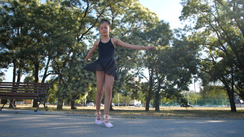 Beautiful Caucasian girl of eight years in black ballet suit dancing ballet in a city park on a sunny summer day. Slow motion 200 fps | Shutterstock HD Video #1057217665