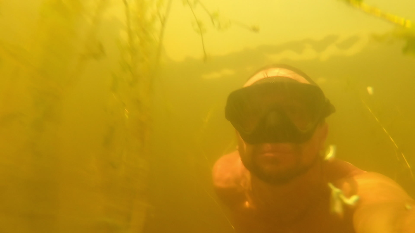 Man swims underwater in a freshwater murky lake with mask | Shutterstock HD Video #1057217959