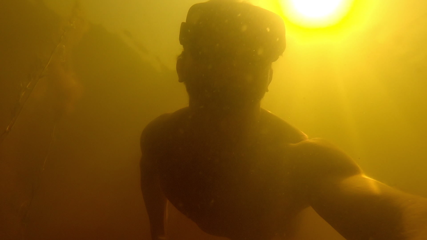 Man swims underwater in a freshwater murky lake with mask | Shutterstock HD Video #1057217986