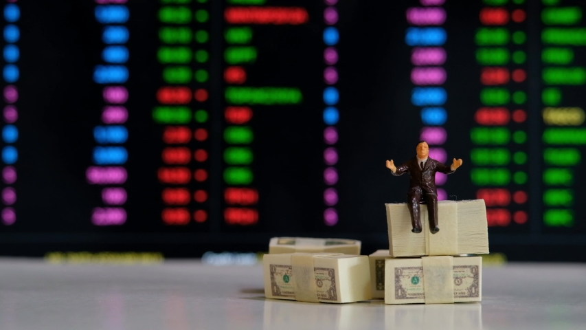 Miniature figure business people or Stock Trader sitting on Dollar Banknotes with at Blur Price Stock Ticker board on background for Graph Analysis   Shutterstock HD Video #1057218037