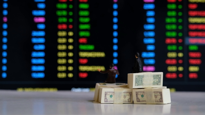 Miniature figure business people or Stock Trader sitting on Dollar Banknotes with at Blur Price Stock Ticker board on background for Graph Analysis   Shutterstock HD Video #1057218040