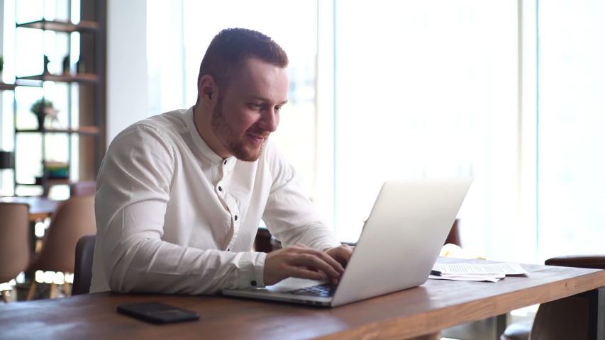 Happy cheerful smiling man wearing casual clothing is working on laptop at desk in office room on background of large window, mobile phone on table. Concept of office working. Shooting in slow motion.   Shutterstock HD Video #1057218217