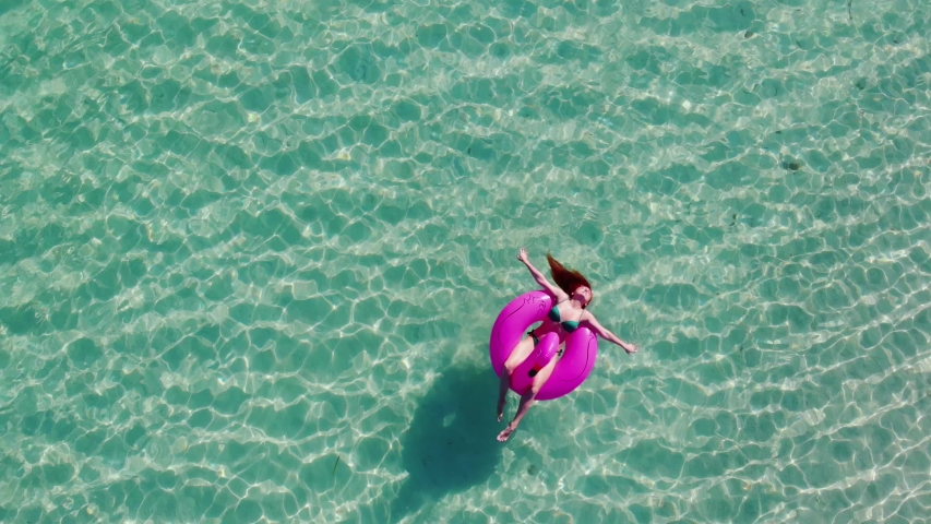 Young relaxed woman in a swimsuit swims in the water on an inflatable flamingo and sunbathes. View from above. The camera rotates. | Shutterstock HD Video #1057219459