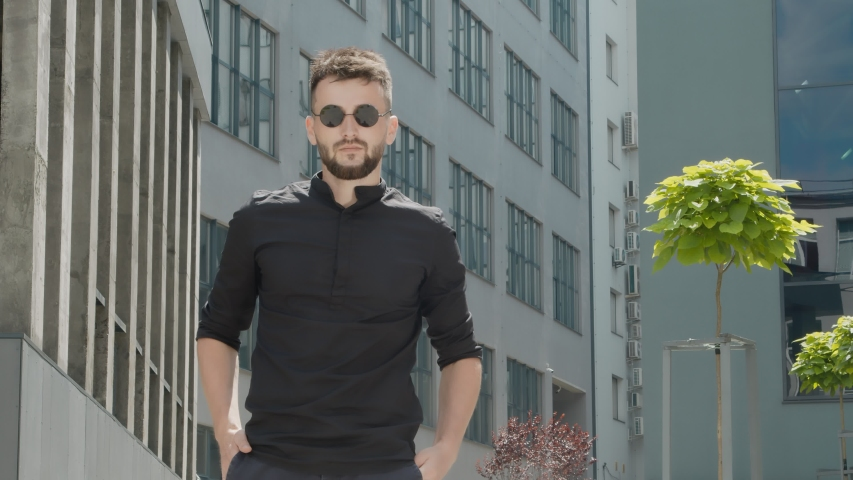 Portrait of a young businessman with glasses holding a mobile gadget and smiling sincerely against the backdrop of modern futuristic city buildings and business center. | Shutterstock HD Video #1057219621