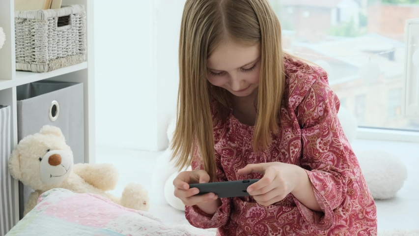 Smiling little girl playing with smartphone in light kids room   Shutterstock HD Video #1057219699