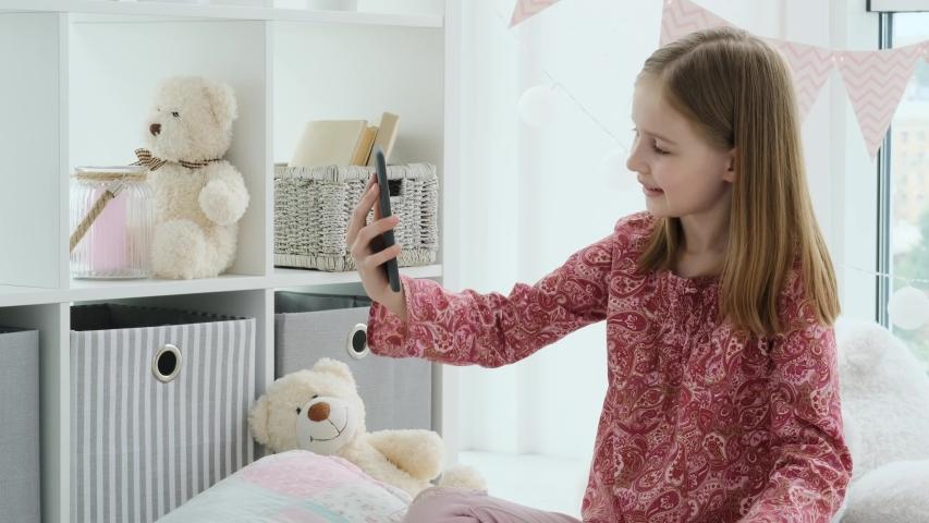 Happy little girl talking via video call using phone indoors   Shutterstock HD Video #1057219714