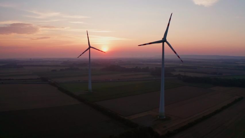 Aerial photography drone shot of two wind turbines in the soft morning light, silhouettes in the early red dawn, sun rising at the horizon, highway with cars in the backgound