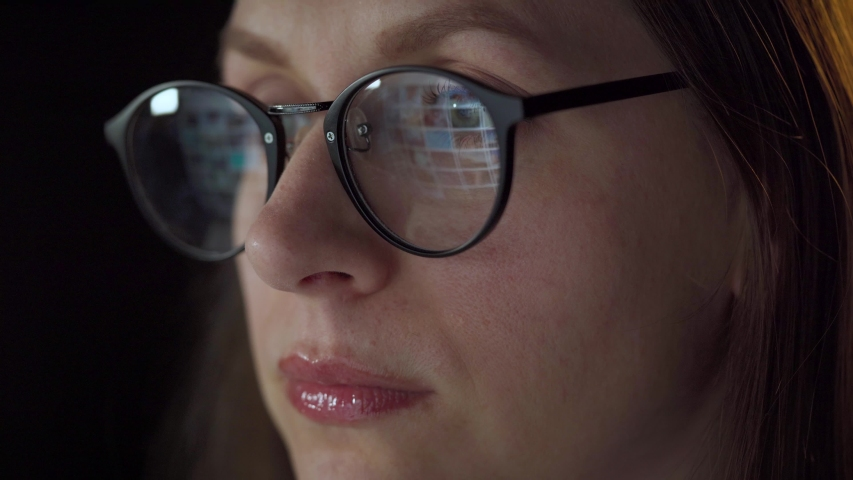 Woman in glasses looking on the monitor and surfing Internet. The monitor screen is reflected in the glasses. Work at night. Home Office. Remote work   Shutterstock HD Video #1057221325