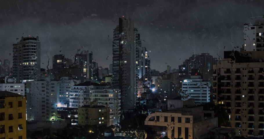 Big city on a rainy night. View from the buildings of the city and the rain running down outside of the window. Animation.