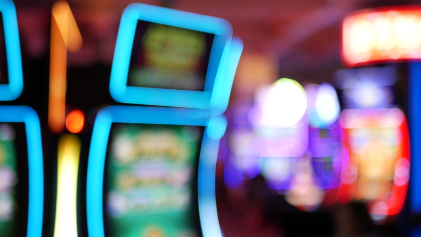 Defocused slot machines glow in casino on fabulous Las Vegas Strip, USA. Blurred gambling jackpot slots in hotel near Fremont street. Illuminated neon fruit machine for risk money playing and betting. | Shutterstock HD Video #1057225480