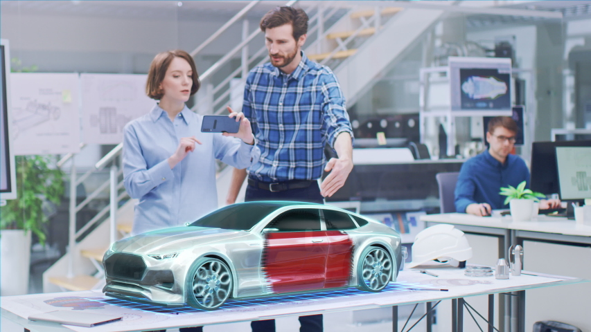 Industrial Design: Automotive Engineer and Designer Working on 3D Electric Car Design, Using Smartphone with Augmented Reality. Graphical Engine, Battery, Chassis, Body Collect into Full Vehicle