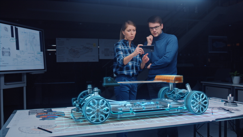 Automotive Engineer Wearing Virtual Reality Headset Working on 3D Electric Car Design, Using Gestures in Augmented Reality. Designing Graphical Parts, Picks Body and Color for the Chassis, Engine