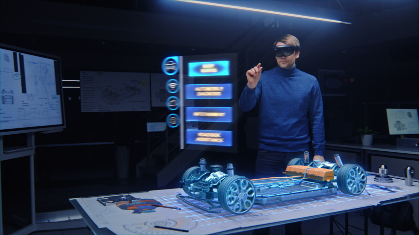 Automotive Engineer Wearing Virtual Reality Headset Working on 3D Electric Car Design, Using Gestures in Augmented Reality He Designs and Manipulates Graphical Parts, Picks Body for the Chassis,Engine