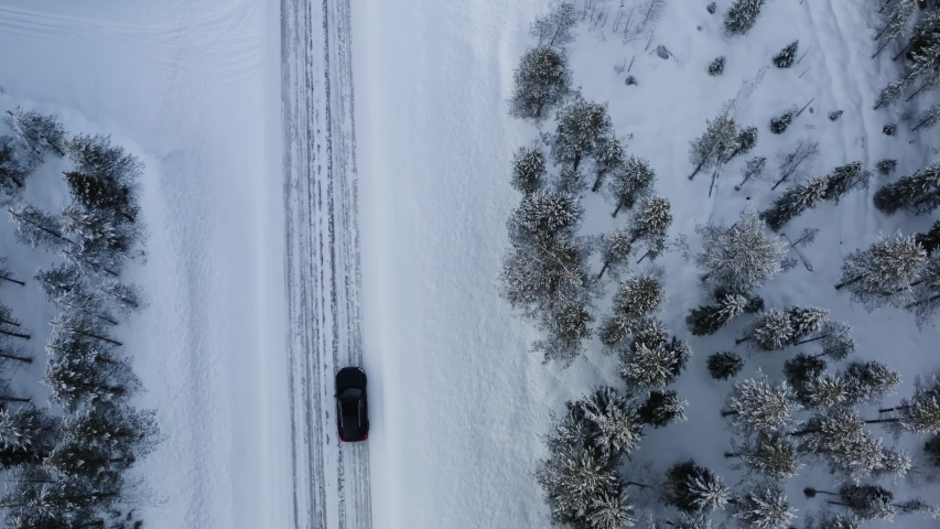 Aerial view of car passing trees and coniferous forest on off road in mountains on winter vacation, bird's eye view of suv driving on snowy path to wild destination landscape | Shutterstock HD Video #1057233769