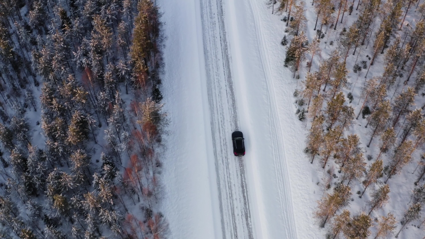 Bird's eye view of car driving on countryside off road on winter vacation getaway, top view of 4x4 suv vehicle on white frozen wanderlust destination on journey. North nature landscape in winter | Shutterstock HD Video #1057235968