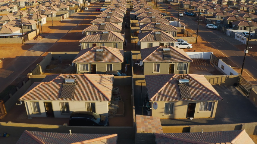 Aerial close-up fly over view of low cost housing in an African township with solar geysers on the rooftops, South Africa