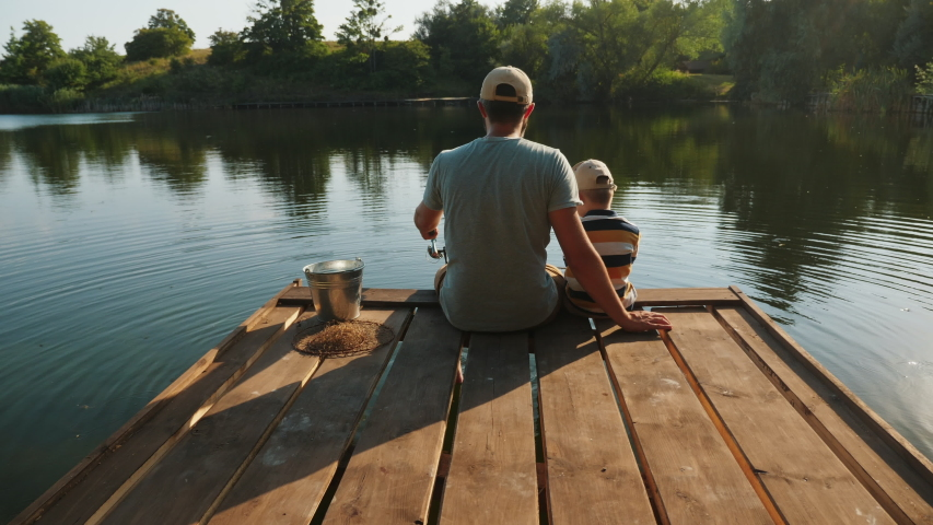 Rear view of a father with his little son are fishing while sitting on a wooden pier by the pond