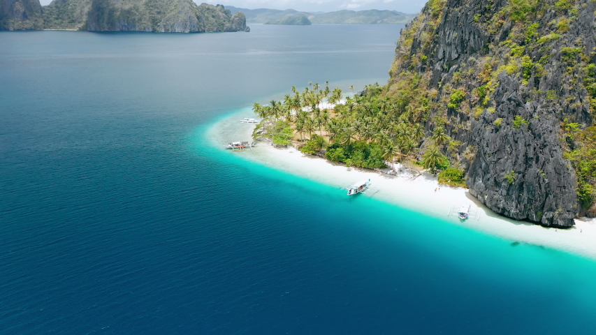 Aerial drone view of tropical Ipil beach, Pinagbuyutan Island, El Nido, Palawan, Philippines. Turquoise blue water, sandy beach and palm trees - vacation, travel tourism concept. | Shutterstock HD Video #1057241494