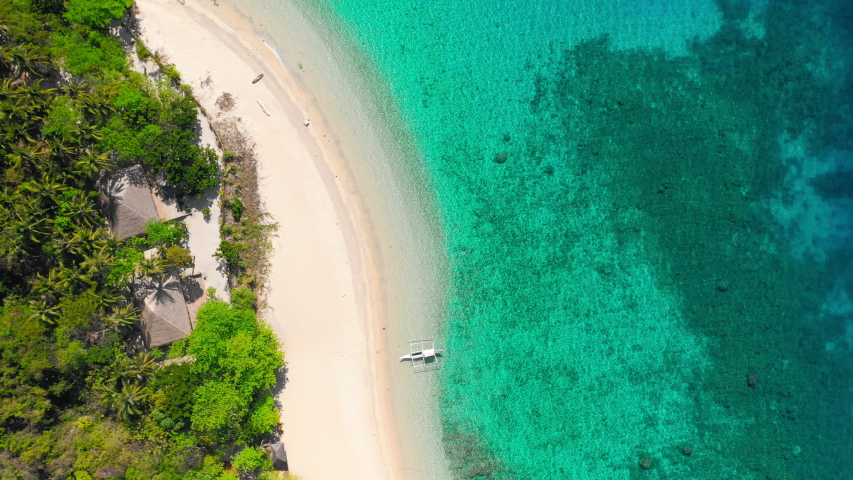 Aerial footage of tropical beach on Helicopter island with palm trees, blue lagoon, azure clear water and coral reef. Lonely tourist boat at white sandy beach. El Nido, Palawan Philippines. | Shutterstock HD Video #1057241500