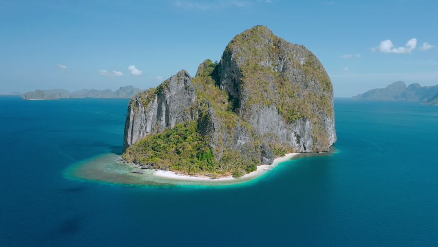 Aerial drone view of Karst limestone rocky Pinagbuyutan Island in blue sea of El Nido, Palawan, Philippines. Tropical Ipil palm beach located in front. | Shutterstock HD Video #1057241542