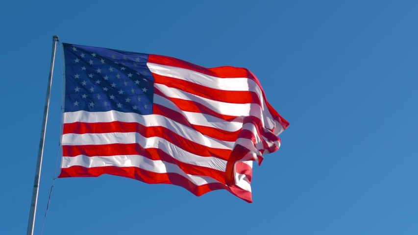 American Flag Waving In Wind Against A Deep Blue Sky. American USA flag on flagpole waving, slow motion. Big American flag gently waving in the wind, slow motion. American flag flying at sunny day