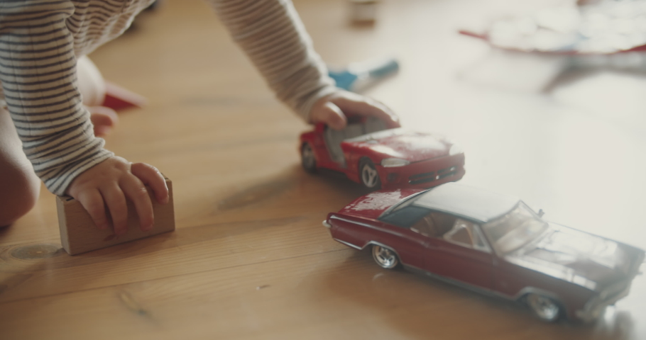 View of childs hands playing red car models and wooden blocks on the floor. Room filled with morning sunlight. Tiny fingers with toys. Royalty-Free Stock Footage #1057242850
