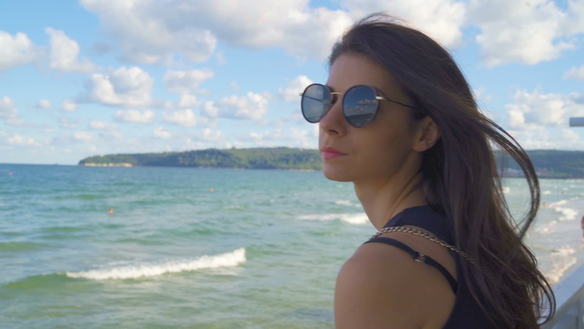 A woman wearing sunglasses and smiling next to water | Shutterstock HD Video #1057243420